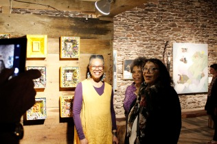 Martina Johnson-Allen and guests with Martina's box constructions and Gwen Strahle's painting at Kings Oaks. Photo by Onyx Clemons