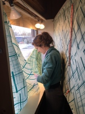 Clara Weishahn installing Bee's Wrap in the Kings Oaks art window at Organnons.